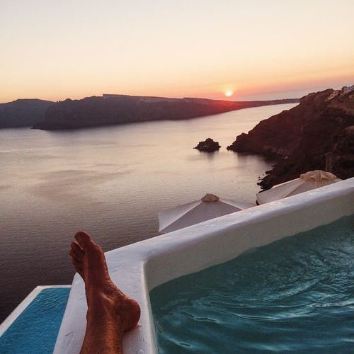 Low section of person by infinity pool and sea against sky during sunset