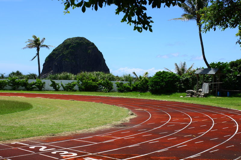 The playground runway beside the small mountain No People Green Red Runway Sunlight Travel Beside Green Color Mountain No People Number Outdoors Playground Running Track Sky Small Mountain Sport Sports Track Tree