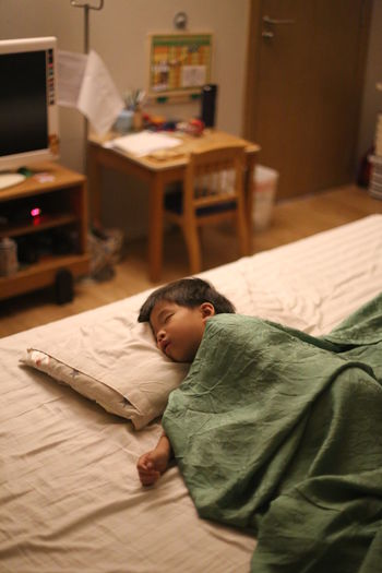 Boy sleeping on bed at home