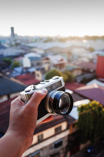 Close-up of hand holding camera against townscape
