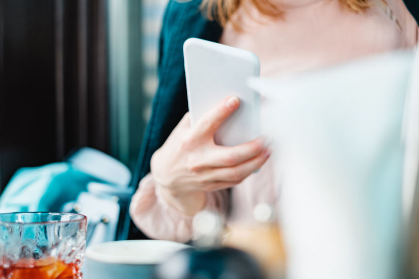 woman using mobile phone at dinner table Food And Drink Mobile Phone Adult Breakfast Coffee Coffee - Drink Coffee Cup Communication Drink Food And Drink Front View Holding Lifestyles Midsection Mug One Person Selective Focus Using Mobile Wireless Technology Women Young Adult