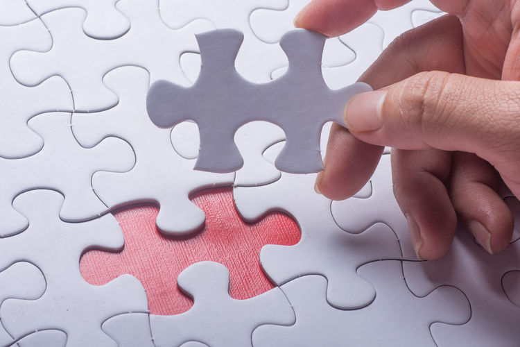 Hand holding piece of blank jigsaw puzzle with red background. Close-up Connection Day Holding Human Hand Indoors  Jigsaw Piece Jigsaw Puzzle Leisure Activity Leisure Games One Person Pattern Puzzle  Solution Strategy White Color