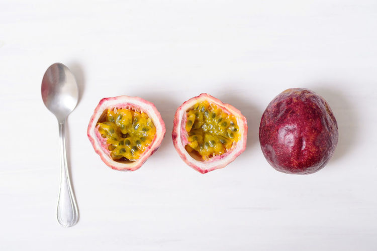 Fresh passion fruit and spoon on white background, tropical and healthy fruit Diet Eating Exotic Food Fresh Freshness Fruit Half Health Healthy Ingredient Juicy Natural Nutrition Organic Passion Ripe Seed Spoon Top View Tropical White Food And Drink Studio Shot Indoors  White Background Eating Utensil Healthy Eating Wellbeing Directly Above Cross Section Close-up Passion Fruit