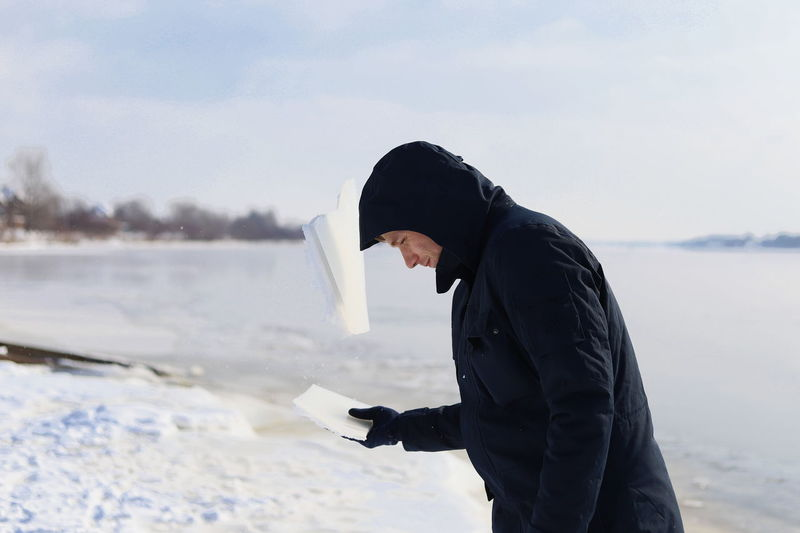 Side view of man breaking ice with head at lakeshore