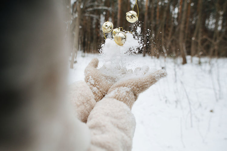 Midsection of woman catching christmas ornament and snow