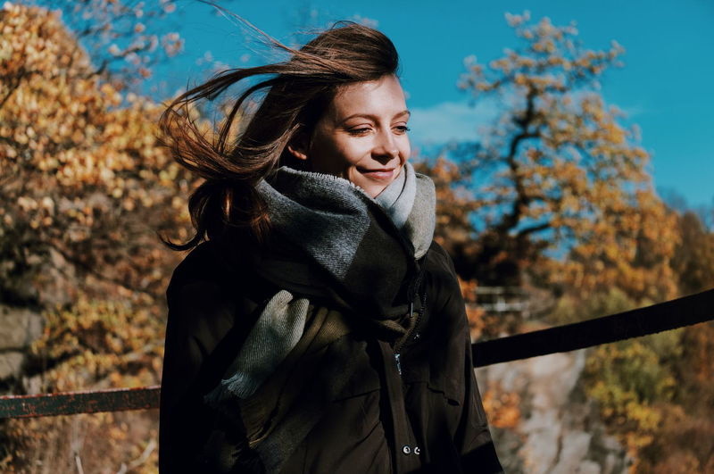 Portrait of smiling woman standing by tree during autumn