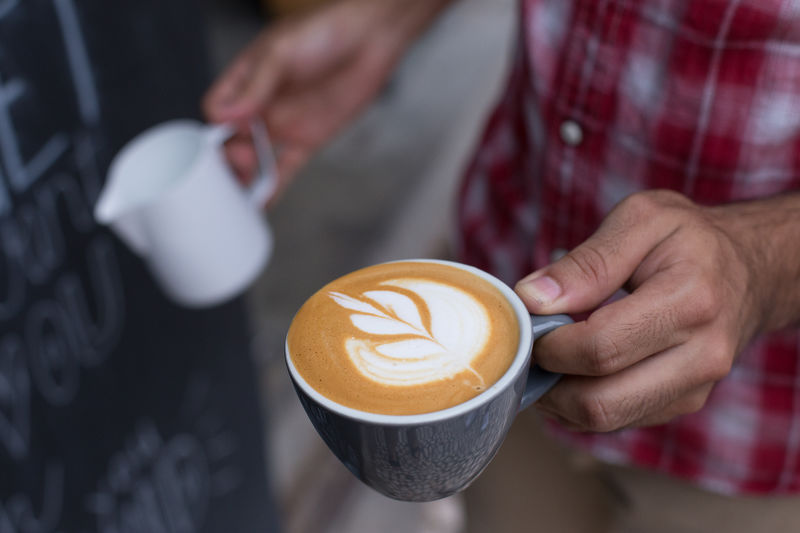 Midsection Of Barista Pouring Milk In Coffee At Cafe