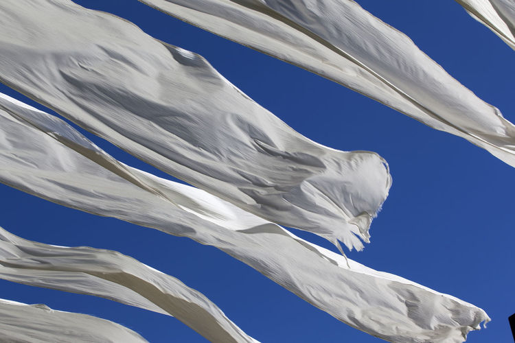 Low angle view of blowing white fabrics against blue sky