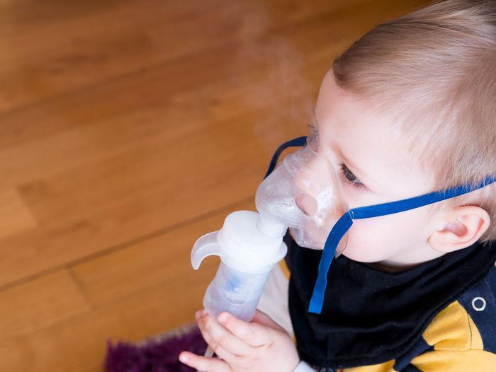 Cute boy wearing oxygen mask on parquet floor