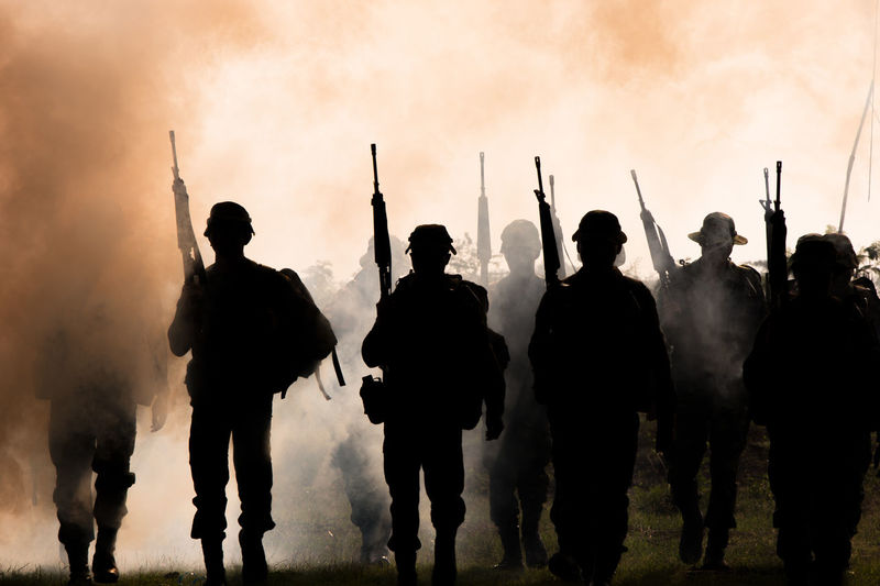 Army soldiers walking against smoke