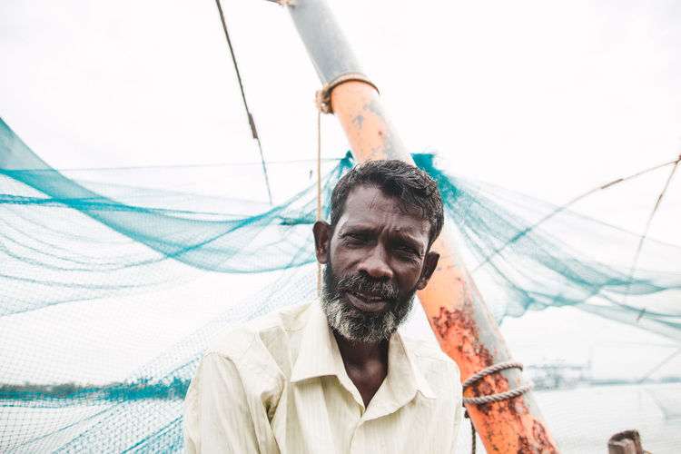 Portrait of fisherman by fishing net