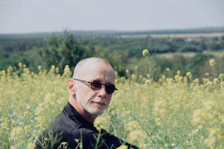 Portrait of man wearing sunglasses sitting amidst plants on land