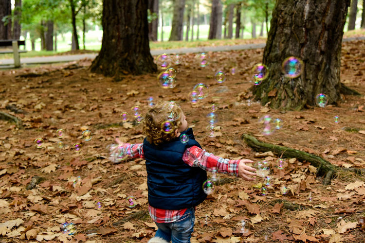 Girl playing in forest during autumn