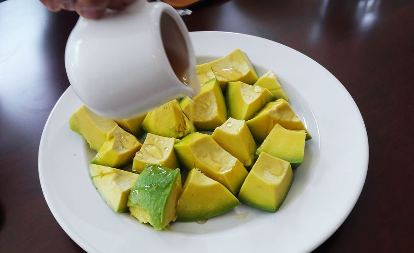 Close-up of jug pouring syrup on chopped avocados in plate at table