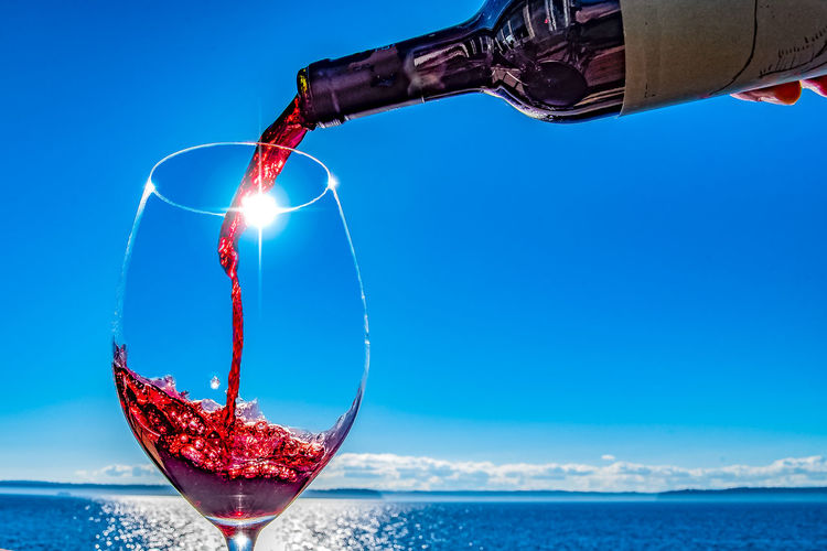 Close-Up Of Person Pouring Wine In Wine Glass At Sunny Seaside