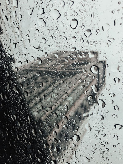 Raindrops on sunroof with blur building background. Drop Wet Water Rain Transparent Glass - Material Window Full Frame Backgrounds RainDrop No People Close-up Rainy Season Nature Indoors  Mode Of Transportation Vehicle Interior Land Vehicle Glass Purity
