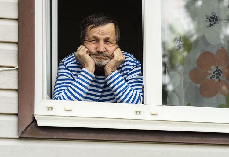 Portrait of man looking through window
