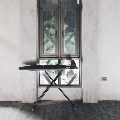 Iron On Ironing Board Against Window At Home
