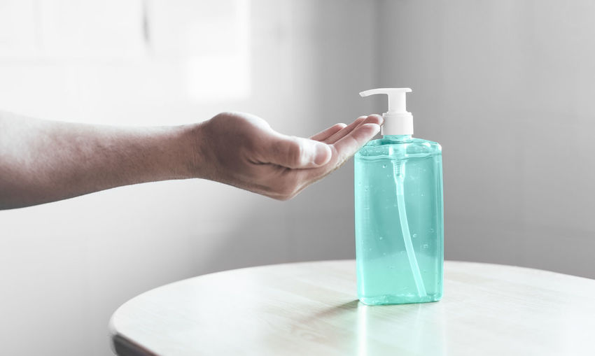 Close-up of hand holding glass bottle on table