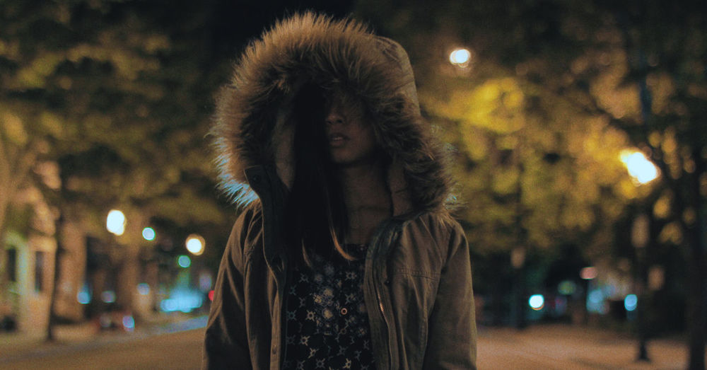Portrait of woman standing against illuminated city at night