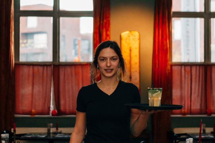 frontal view of a cheerful brunette barista holding a tray with a drink Employee Tray Uniform Adult Bartender Casual Clothing Drink Emotion Food And Drink Front View Girl Glass Hairstyle Happiness Indoors  Looking At Camera One Person Portrait Real People Smiling Table Waist Up Women Young Adult Young Women