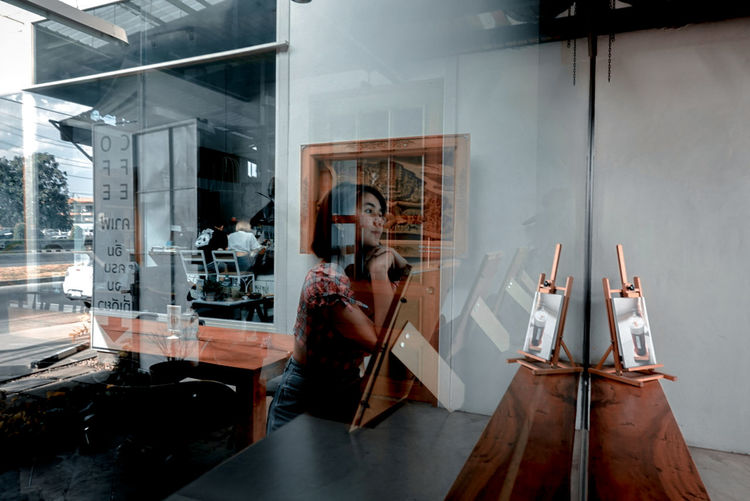 Midsection of woman sitting in glass window