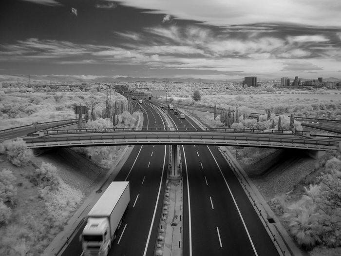 Infrared image of bridge over road against cloudy sky