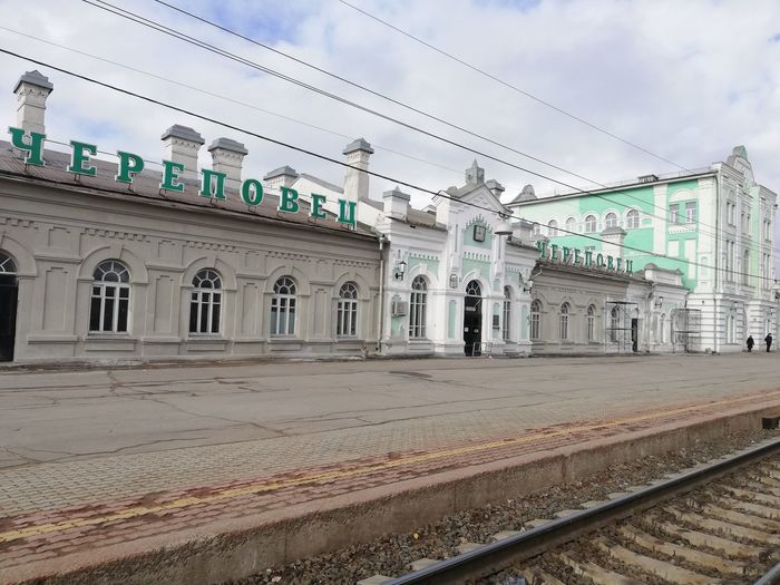 Railroad station platform by city against sky