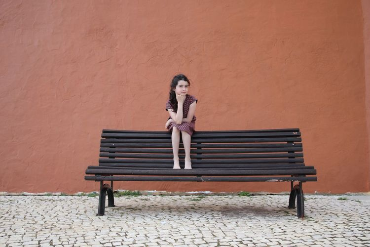 EyeEm Selects Sitting Young Women Portrait Women Full Length Front View Waiting Bench Wooden Fashion Model Fashion Show Mini Dress Artist's Model Posing Park Stiletto Blooming EyeEmNewHere Focus On The Story
