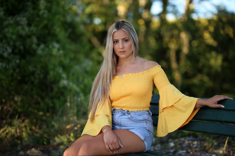 Beautiful young woman with yellow hair against trees