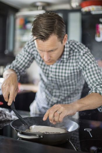 Midsection of man holding hands in kitchen