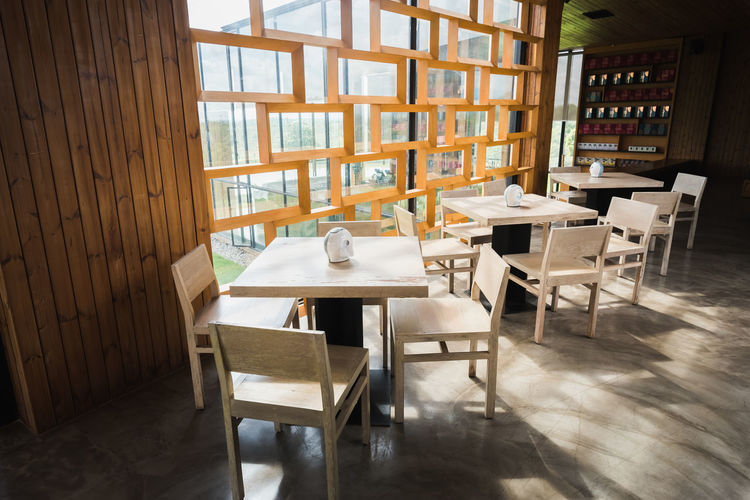 Empty chairs and table arranged in cafe