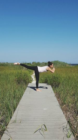 Woman Exercising On Boardwalk Against Clear Blue Sky
