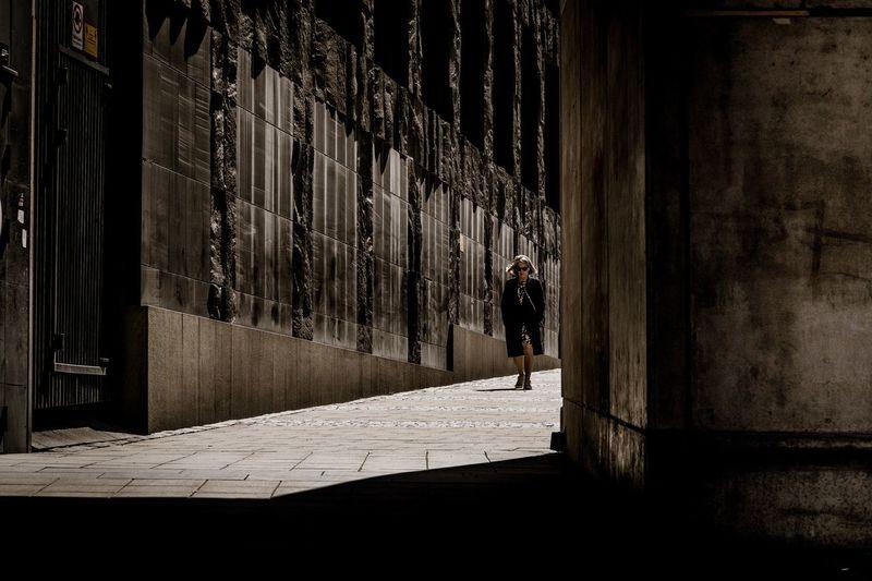 Rear view of man walking amidst buildings in city