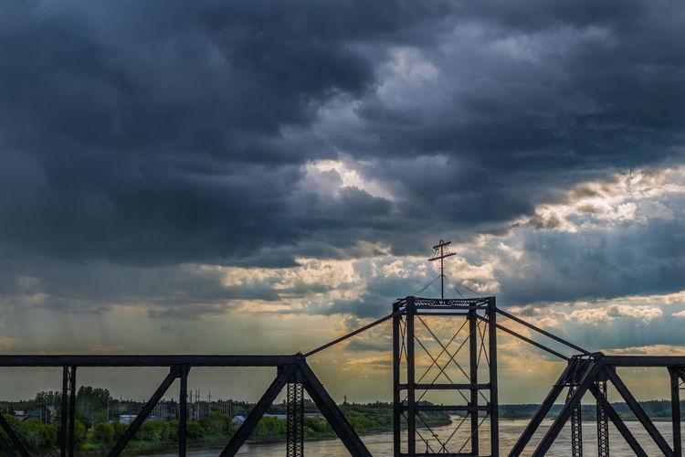 Silhouette of ferris wheel against cloudy sky