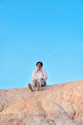 Low angle view of woman sitting on mountain against clear blue sky