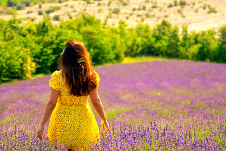 Rear view of woman with yellow flowers on field