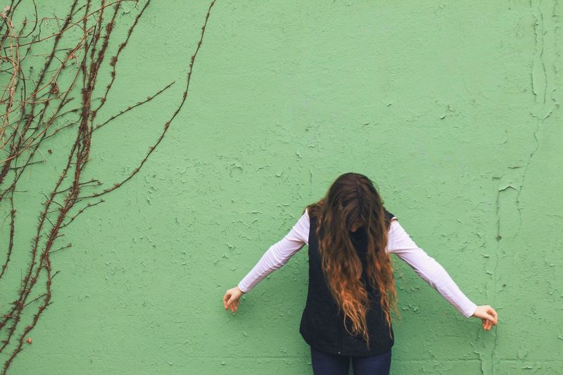Young woman standing against green wall