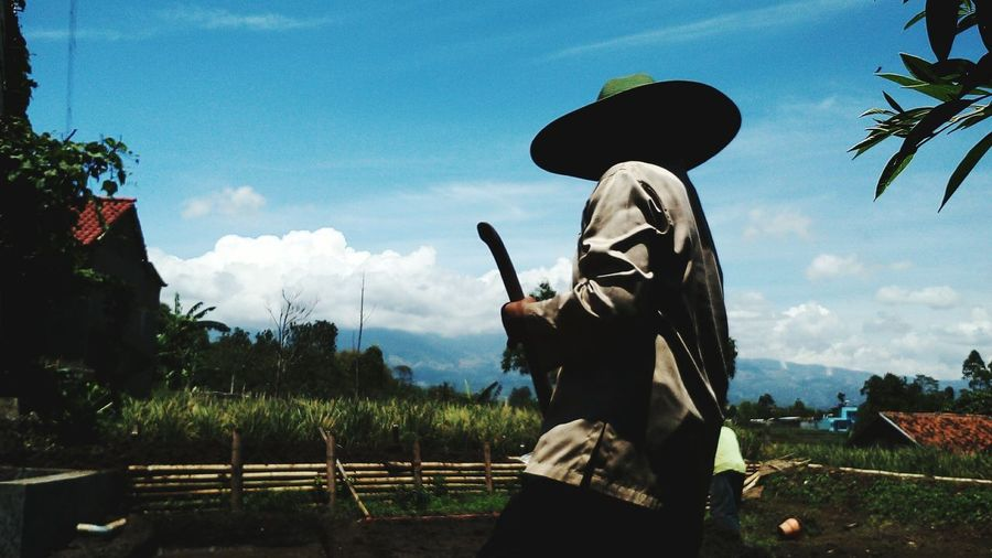 Side View Of Farmer Standing On Field Against Sky