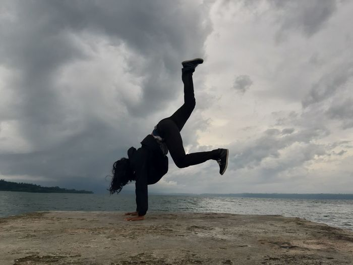 Woman doing handstand on pier over sea against sky