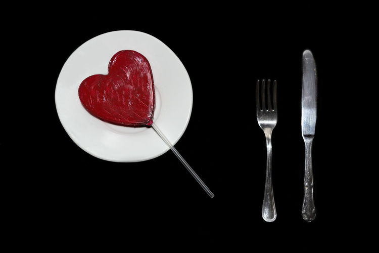 Red heart lollipop ready to eat on a white plate with stainless steel fork and knife, on black background, Love concept Indoors  No People Studio Shot Backgrounds Copy Space Wallpapaer Heart Shape Lollipop Red In Love Romance Romantic Celebrate Celebration Object Colorful Fun Tasty Delicious Plate Fork Knife White Blackandwhite