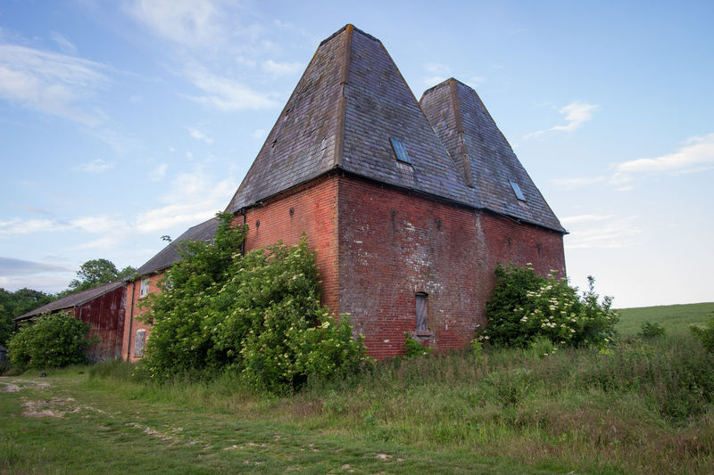 Oast House, Garden Of England, Kent, England. Architecture Sky Built Structure Nature No People Plant Hops Beer Brewing Iconic Buildings Vivid International Getty Images EyeEm Gallery Travel Destinations Tourism Sunrise Countryside Rural Scene History Grass Cloud - Sky Building Exterior Field Land Building Day Tree Outdoors Abandoned Old Growth Green Color Landscape