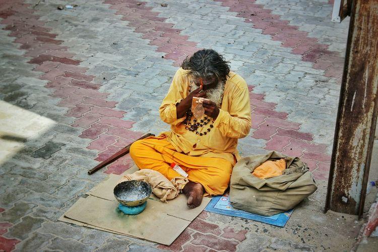 High angle view of sadhu sitting on cardboard at paved walkway