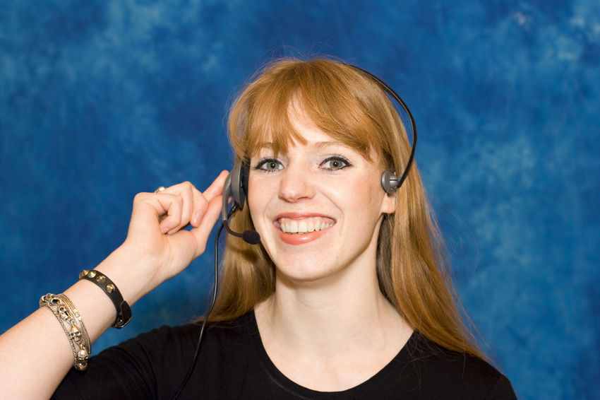 Young businesswoman wearing headset - smiling Business Businesswoman Call Center Close-up Communication Connection Happy Head And Shoulders Headset Headshot Listening Looking At Camera Occupation One Woman Only One Young Woman Only Portrait Red Hair Redhead Service Smiling Technology Wireless Technology Woman Working Young