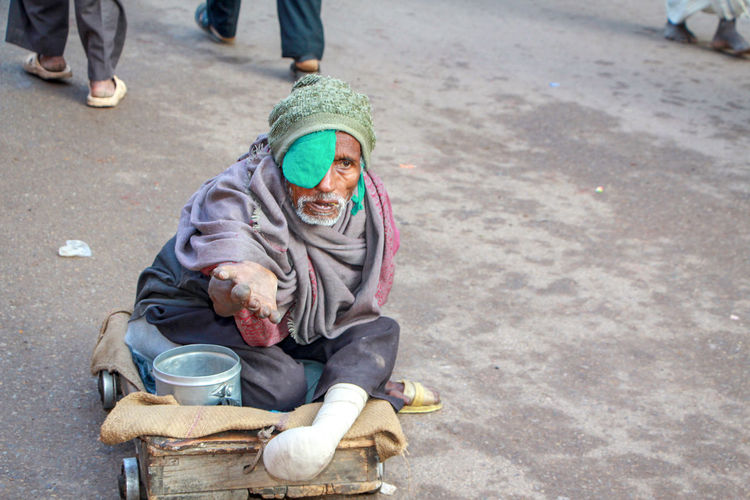 High angle view of handicapped senior man begging on road