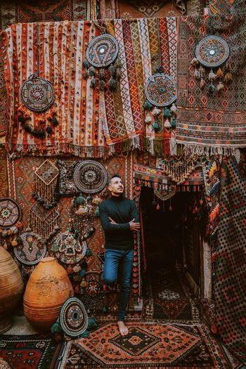 Full length of man standing against wall in market. turkish carpets