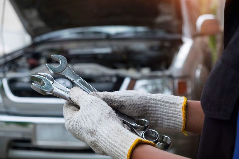 Cropped hand of mechanic holding equipment