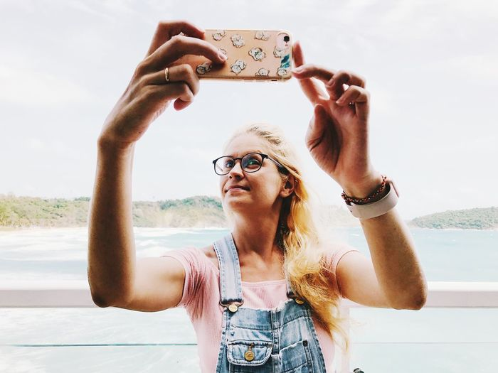 Woman photographing with mobile phone against sea and sky