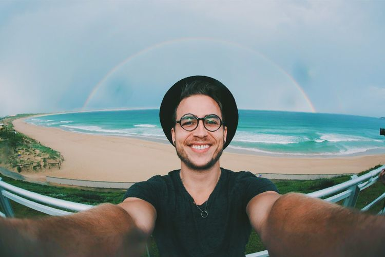 Portrait of smiling man taking selfie at the beach