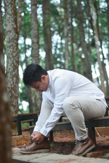 Side view of young man standing by tree in forest